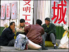 Migrant workers rest on a Beijing street