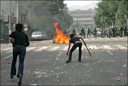 Supporters of opposition leader Mir Hossien Mousavi set fire to a barricade as they hurl stones at riot police during a protest in Tehran on Saturday June, 20, 2009