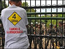 Simpatizante del presidente Manuel Zelaya se para frente a soldados que resguardan el palacio presidencial.
