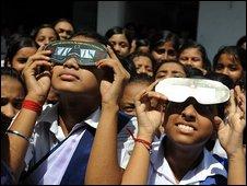 Personas utilizando máscaras para ver el eclipse