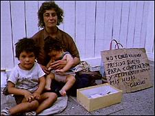 Una mujer pide dinero en la calle.