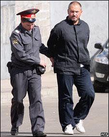 Милиционер конвоирует одного из подозреваемых в захвате судна Arctic Sea у здания Генеральной прокуратуры в Москве 26 августа 2009 года