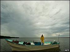 Un pescador se apresta a sacar su bote del agua ante la llegada del huracán