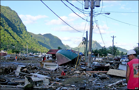 A resident walks past debris in a playground and a tennis park left by the tsuami that struck early Tuesday Sept. 29, 2009 in Pago Pago, American Samoa