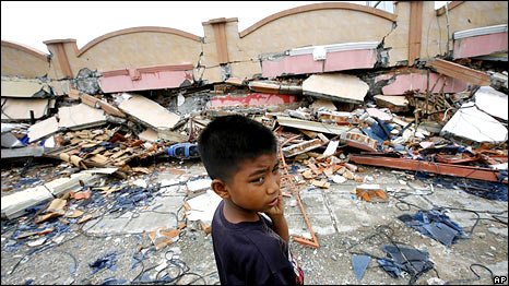 A boy stands near a building flattened by an earthquake in Padang, West Sumatra, Indonesia, Thursday, Oct. 1, 2009