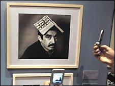 La gente saca fotos con sus celulares de fotografías de Gabriel Garcia Marquez