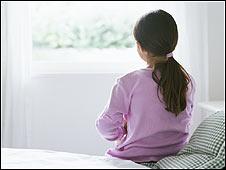 Niña sentada en una cama observa la ventana (Foto: Archivo)