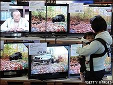 Mujer mirando televisores en una tienda de San Francisco