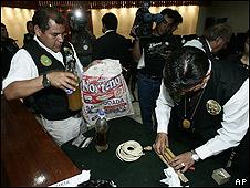 Policías peruanos muestran botellas que contienen grasa humana