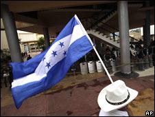 Un hombre carga la bandera de Honduras