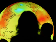 Silhouettes of people in front of an illuminated model of planet Earth