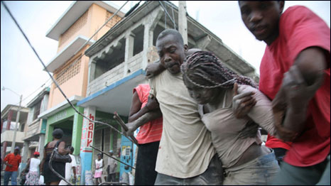 A Haitian woman is helped after being trapped in rubble in Port-au-Prince, Haiti