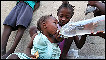 A two year old Haitian girl is given water by her sister