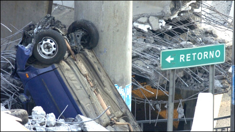 An overturned vehicle sits amidst the rubble of a collapsed elevated highway in Santiago, Chile