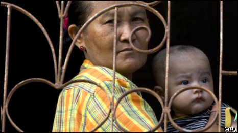 A Burmese migrant woman holds a baby looking out of the window of her apartment in a Burmese community in Mahachai, Thailand on February 25, 2010