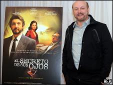 O diretor Juan José Campanella posa ao lado do cartaz do filme 'O Segredo dos Seus Olhos'