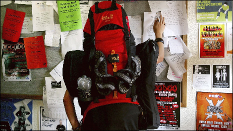 A backpacker checks a noticeboard in Australia