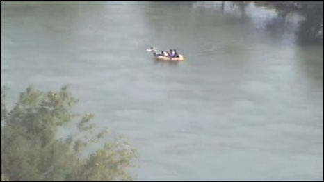 Still from webcam footage of people crossing a river from Mexico to Texas