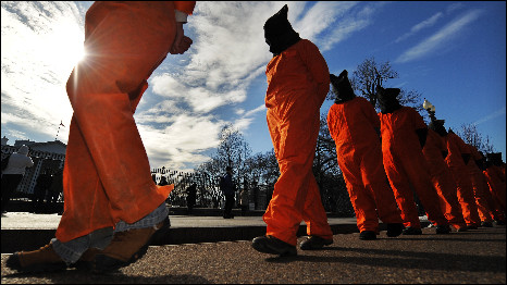 Demonstrators dressed as Guantanamo Bay prisoners
