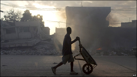 A man pushes a wheelbarrow through Port-au-Prince, Haiti, 31 March 2010