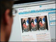 Homem olha tela de computador com fotografias no centro da  polêmica
