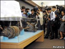 Cámaras y fotógrafos surcoreanos toman imágenes de un torpedo norcoreano.