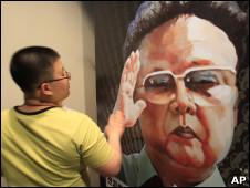 Un surcoreano pasa frente a una pintura de Kim Jong-Il