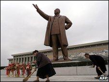 Phụ nữ quét dọn các bậc thềm ở chân tượng Kim Nhật Thành