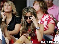 Victoria Beckham lee un mensaje de texto durante un partido de fútbol