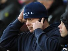 Fanático de fútbol habla por celular durante un partido