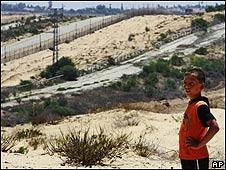 Niño palestino mira la frontera entre Israel y Gaza