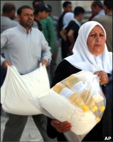 Palestinos transportan bolsas con ayuda en la Franja de Gaza.