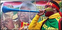 Un aficionado sudafricano enfrente de una imagen de Nelson Mandela