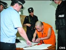 身穿囚服的彭志民在签字画押