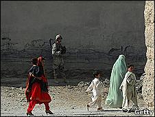 Mujeres y niños pasean delante de un soldado afgano