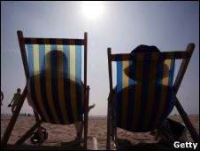 Casal toma banho de sol em praia na Grã-Bretanha