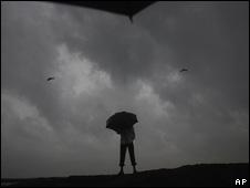 Hombre con paraguas bajo una inminente tormenta