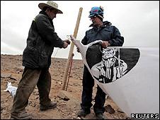 Funcionários da mina San José colocam bandeira em homenagem aos 33 trabalhadores presos (Reuters)