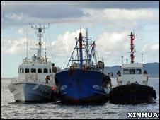 被日本海岸自卫队船只夹在中间的被扣押中国渔船