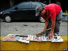 Un vendedor de periódicos arregla los diarios