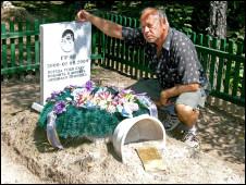 Мужчина сидит у памятника на кладбище