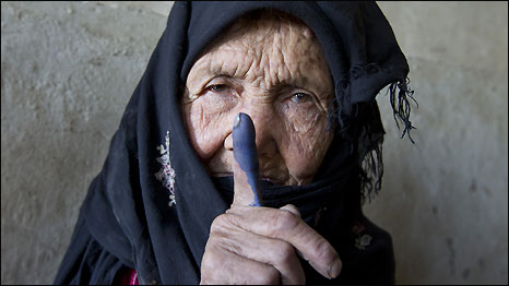 An elderly woman shows off her inked finger after she cast her vote in Afghanistan's elections in September 2010.