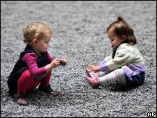 """两个女童在""""葵花籽地毯""""上玩耍。"""