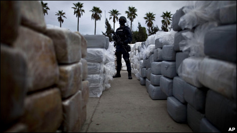 A police officer stands guard next to packages of seized marijuana in Tijuana, Mexico on Monday October, 18, 2010