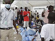 Gente recibe suero en el estacionamiento del hospital San Nicolás en Saint-Marc, Haití