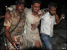 Militar e voluntário levam ferido de explosão em Karachi