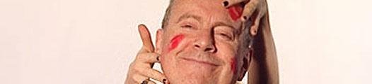 El rostro de un hombre con marcas de labios rojos y unas manos que lo acarician
