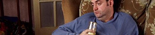 Un hombre recostado en un sofá con una bebida en la mano
