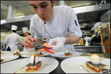 chef preparing food on plates in a kitchen