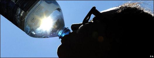 Mujer bebe agua embotellada